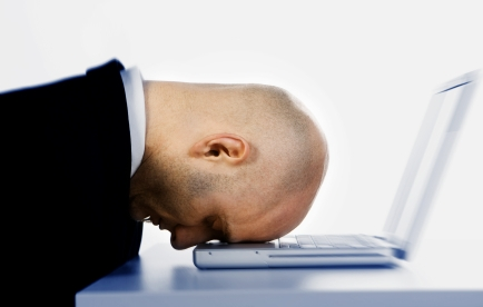 A stressed bald businessman with his forehead resting on the laptop computer keyboard.